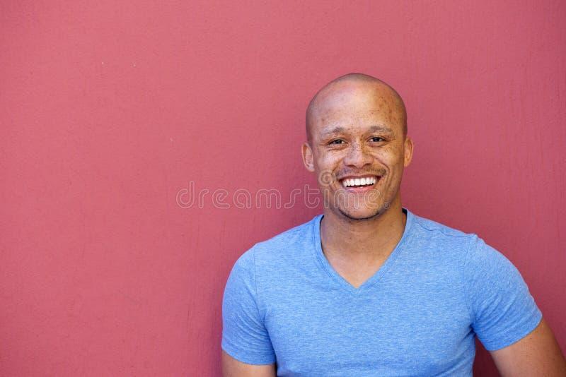 Stilig afrikansk amerikanman som ler mot röd bakgrund fotografering för bildbyråer