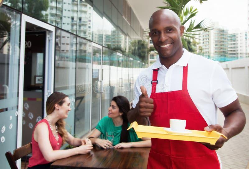 Stilig afrikansk amerikanuppassare på arbete i en restaurang royaltyfri foto