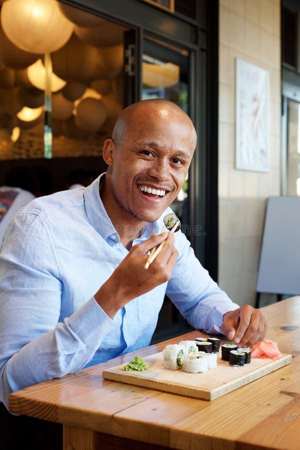 Stilig afrikansk man som äter sushi royaltyfria bilder