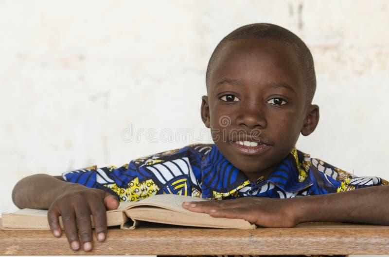 Stilig afrikansvartpojke som studerar en bok i Bamako, Mali royaltyfri fotografi