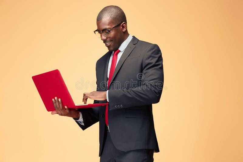 Stilig afro- amerikansk man som använder en bärbar dator arkivfoton