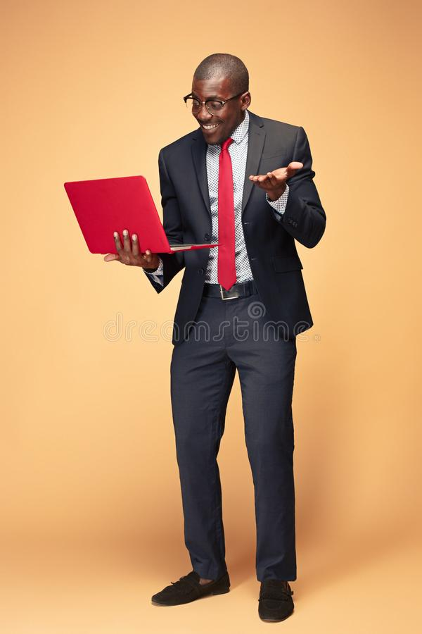 Stilig afro- amerikansk man som använder en bärbar dator royaltyfri bild