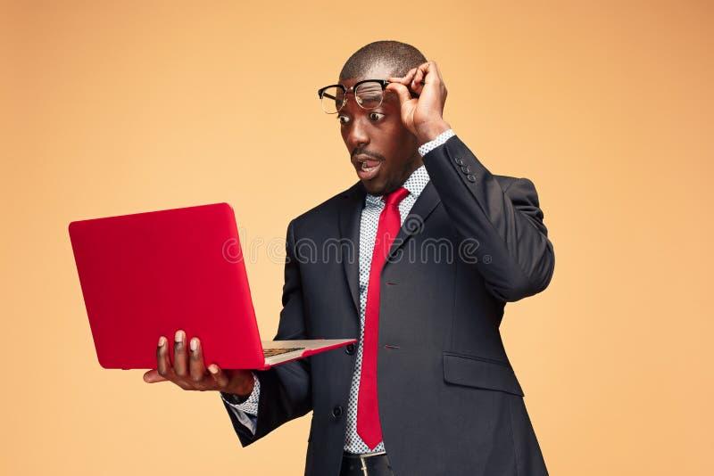 Stilig afro- amerikansk man som sitter och använder en bärbar dator royaltyfri bild