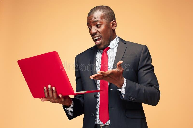 Stilig afro- amerikansk man som sitter och använder en bärbar dator royaltyfria bilder