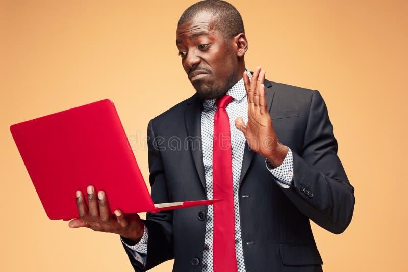 Stilig afro- amerikansk man som sitter och använder en bärbar dator royaltyfri foto