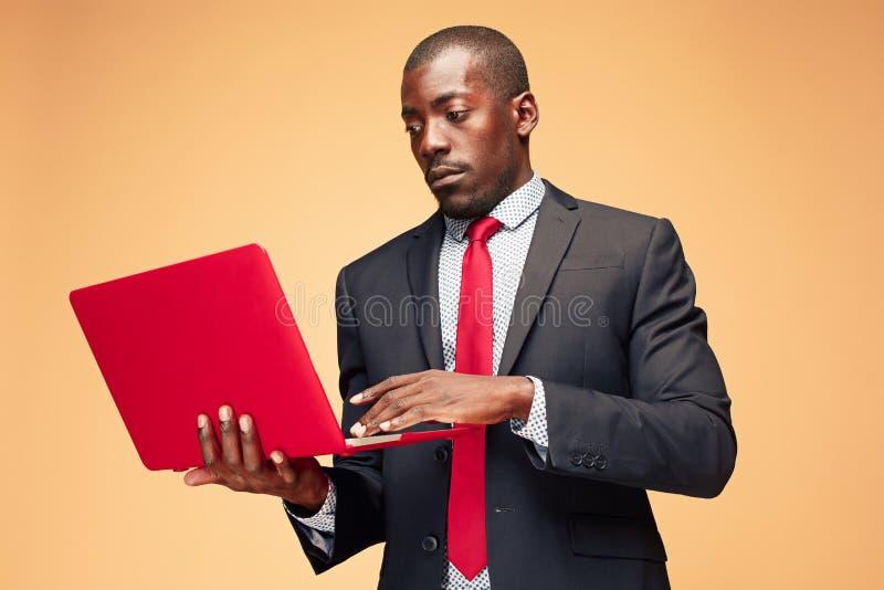 Stilig afro- amerikansk man som sitter och använder en bärbar dator royaltyfria foton