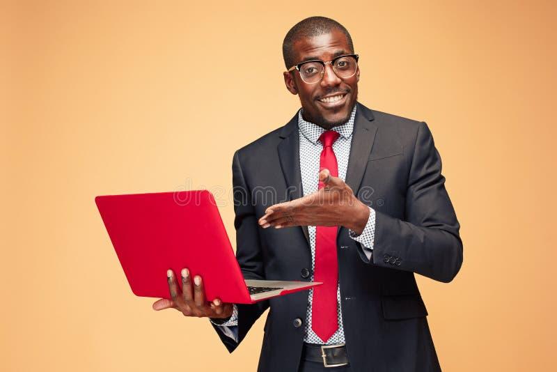 Stilig afro- amerikansk man som sitter och använder en bärbar dator arkivbild