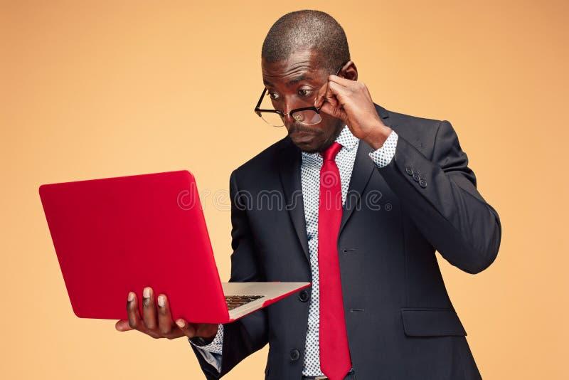 Stilig afro- amerikansk man som sitter och använder en bärbar dator royaltyfri fotografi