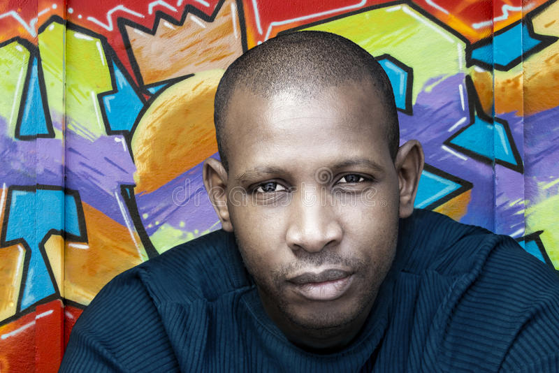 Stilig afro- man framme av en grafittivägg arkivbilder