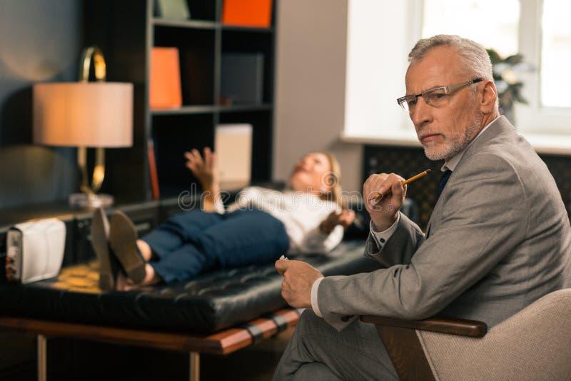 Stilig allvarlig grå färg-haired psykiater som sitter i hans kontor royaltyfria bilder