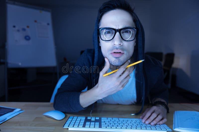 Stilig allvarlig man som rymmer hans haka arkivfoto