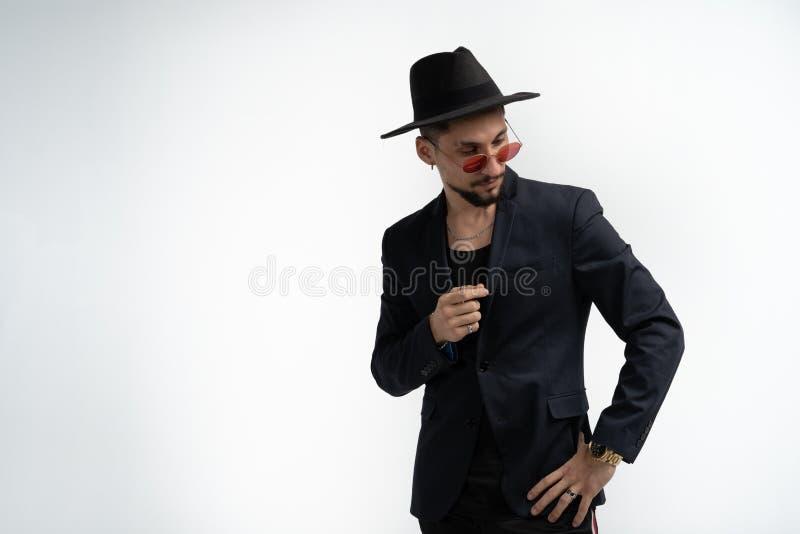 Stilig allvarlig sk?ggig man i svart dr?kt och hatt, i r?tt posera f?r solglas?gon som isoleras mot vit bakgrund som ser arkivbilder