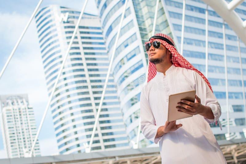 Stilig arabisk håll för affärsman den digitala minnestavlan och se till vänstra sidan Arabiskt anseende för affärsman utanför kon fotografering för bildbyråer