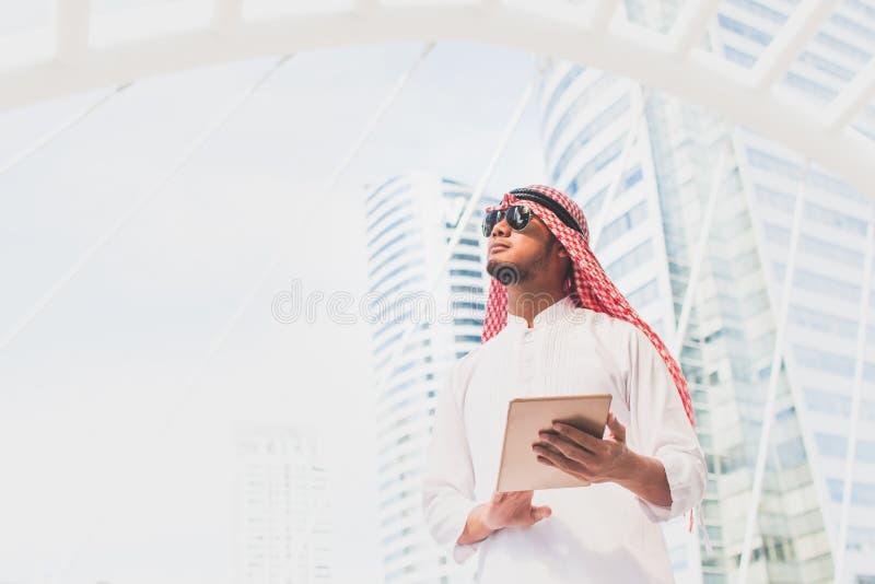Stilig arabisk håll för affärsman den digitala minnestavlan och se till vänstra sidan Arabiskt anseende för affärsman utanför kon arkivbilder