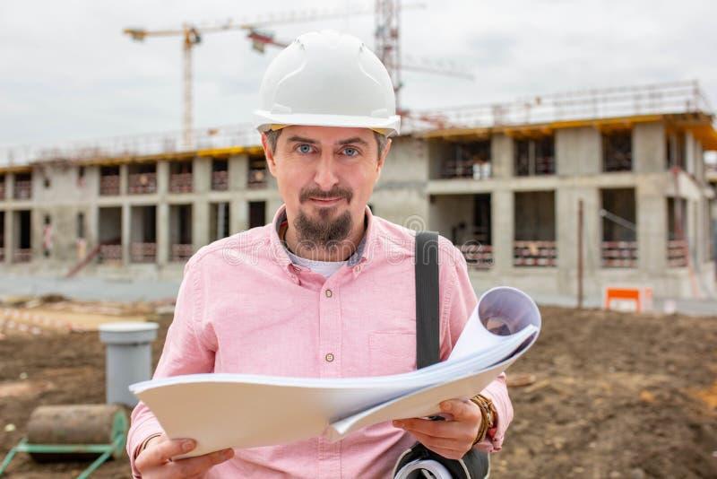 Stilig arkitekt eller arbetsledare som utomhus står på en byggandeplats som rymmer en ritning i hans händer som ser royaltyfri foto