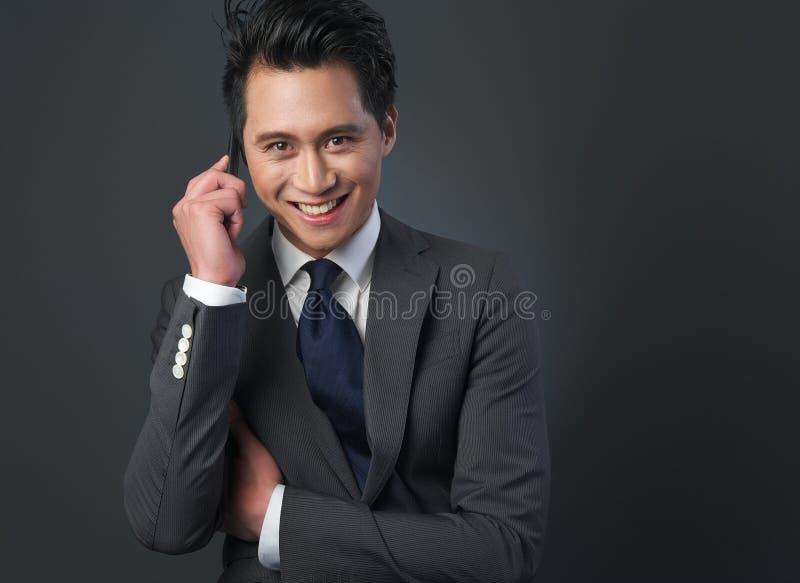 Stilig asiatisk affärsman som ler på telefonen royaltyfri foto