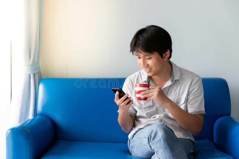 Stilig asiatisk man som använder mobiltelefonen, medan dricka något kaffe och sitta på den blåa soffan arkivbilder