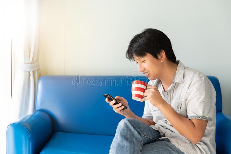 Stilig asiatisk man som använder mobiltelefonen, medan dricka något kaffe och sitta på den blåa soffan royaltyfri fotografi