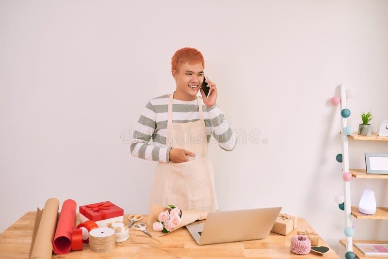Stilig asiatisk manlig blomsterhandlare som talar vid mobiltelefonen på arbetsplatsen royaltyfria bilder