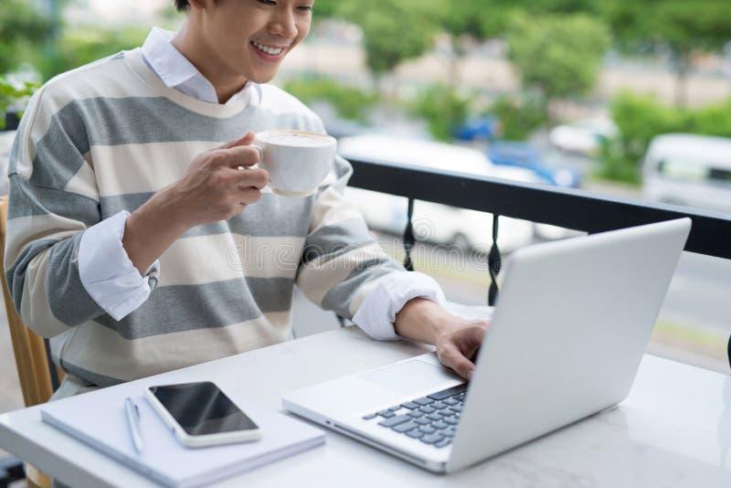 Stilig asiatisk ung man som arbetar på bärbara datorn och ler medan enj arkivfoton