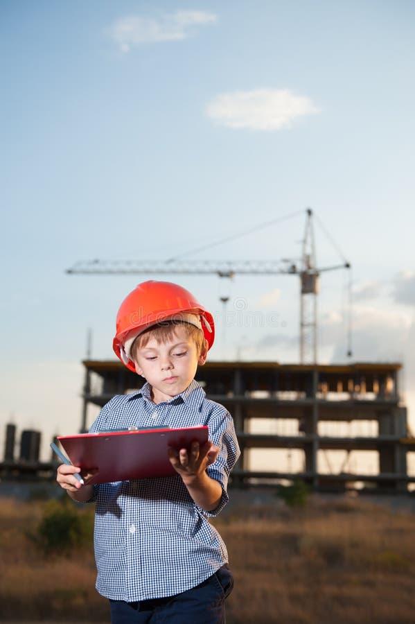 Stilig bärande hjälm för liten unge på byggnad med kranbakgrund arkivbilder