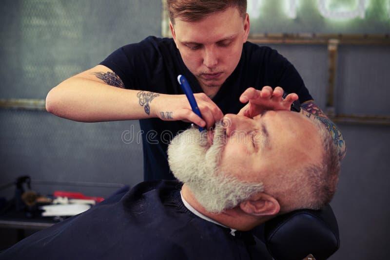 Stilig barberare som rakar den skäggiga mannen royaltyfri bild