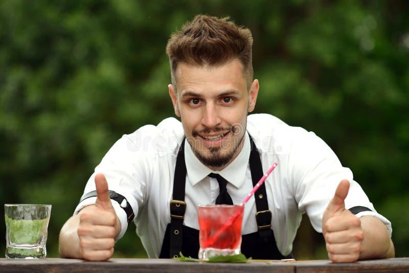 Stilig bartender som står nära stångräknare och tummar upp, selecti royaltyfri foto