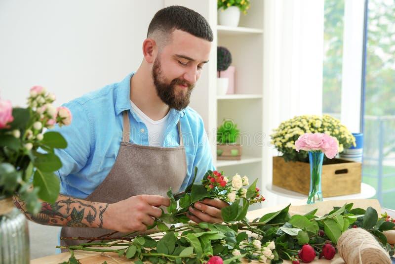 Stilig blomsterhandlare som förbereder buketten royaltyfria bilder