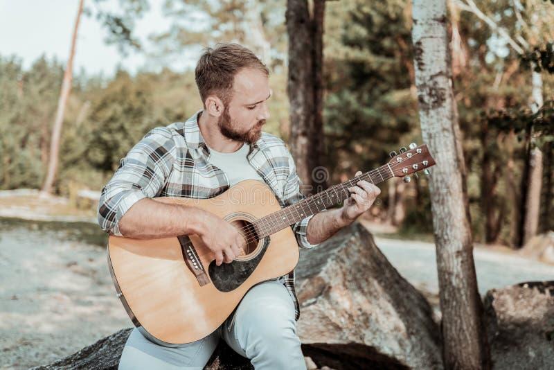 Stilig blondin-haired skäggig inspirerad mankänsla, medan spela gitarren arkivbilder