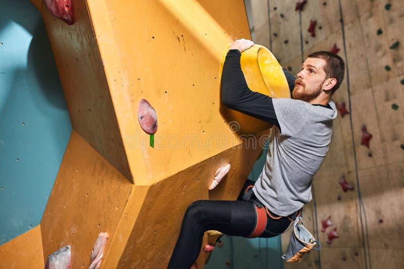 Stilig boulderer som hänger på stor håll på den färgrika klättraväggen royaltyfria foton