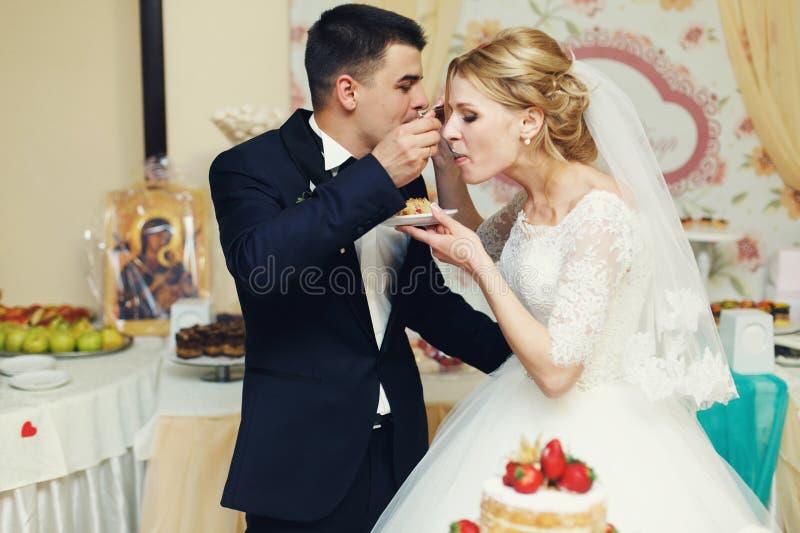Stilig brudgum för lyckliga brölloppar och blondinbrud som äter delikatessaffär royaltyfri bild