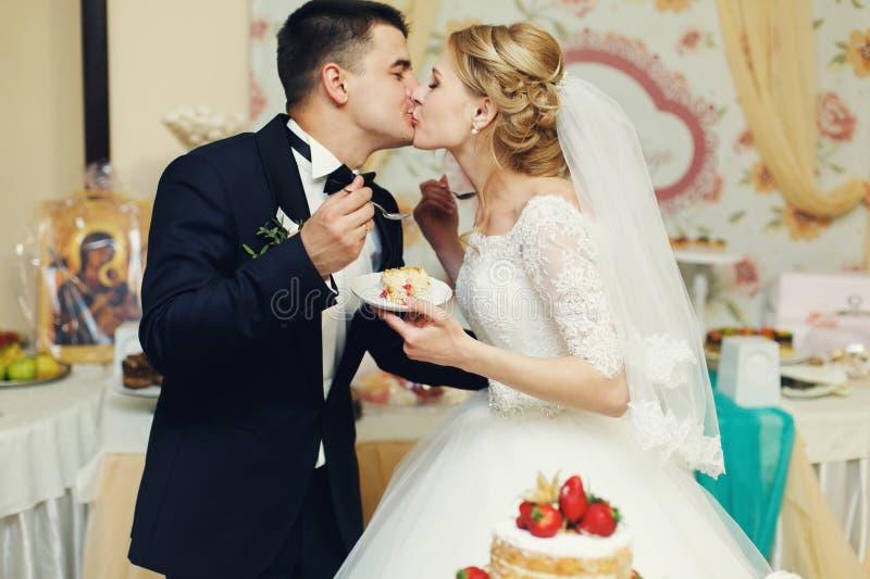 Stilig brudgum för lyckliga brölloppar och blondinbrud som äter delikatessaffär royaltyfri fotografi
