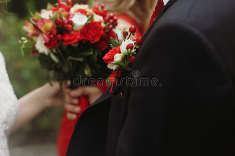 Stilig brudgum i den hållande bröllopbuketten för stilfull svart dräkt, wh arkivbilder