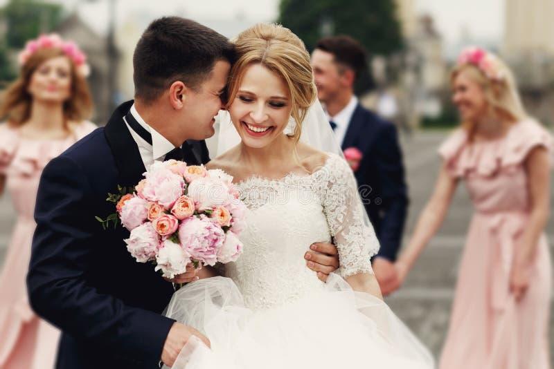 Stilig brudgum i dräkt som kramar den eleganta blonda bruden med bridesm royaltyfri foto