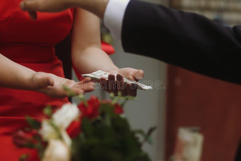 Stilig brudgum i elegant svart betala för dräkt- och bröllopbukett arkivbild