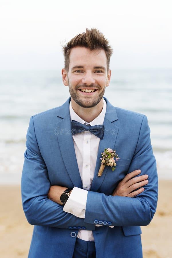 Stilig brudgum som ler på stranden royaltyfria bilder