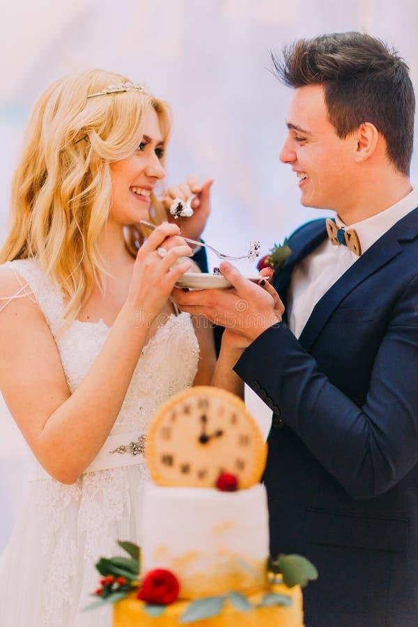 Stilig brudgum som matar hans härliga blonda brud med bröllopstårtan royaltyfria foton