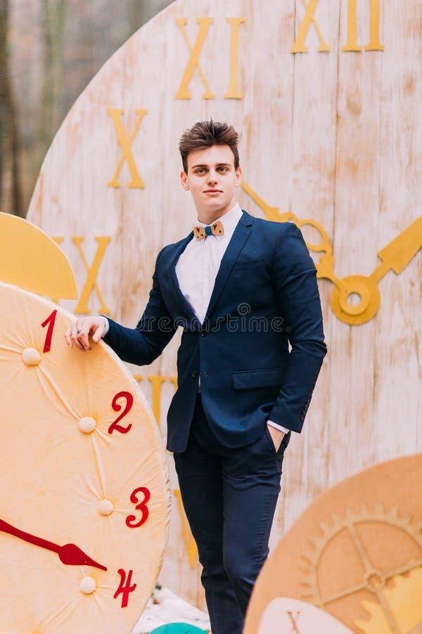 Stilig brudgum som poserar i de dekorativa klockorna för höstskog på bakgrund arkivfoto