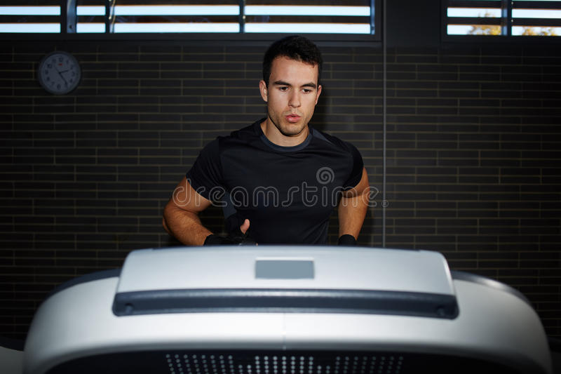 stilig brunettman på genomköraren i idrottshallspring som är snabb på en trampkvarn arkivbild