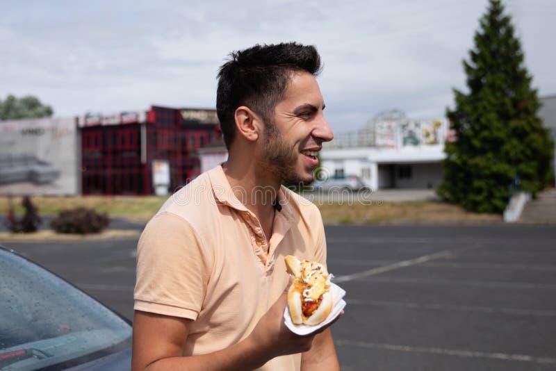 Stilig brunettman som äter varmkorven i parkeringen arkivfoto
