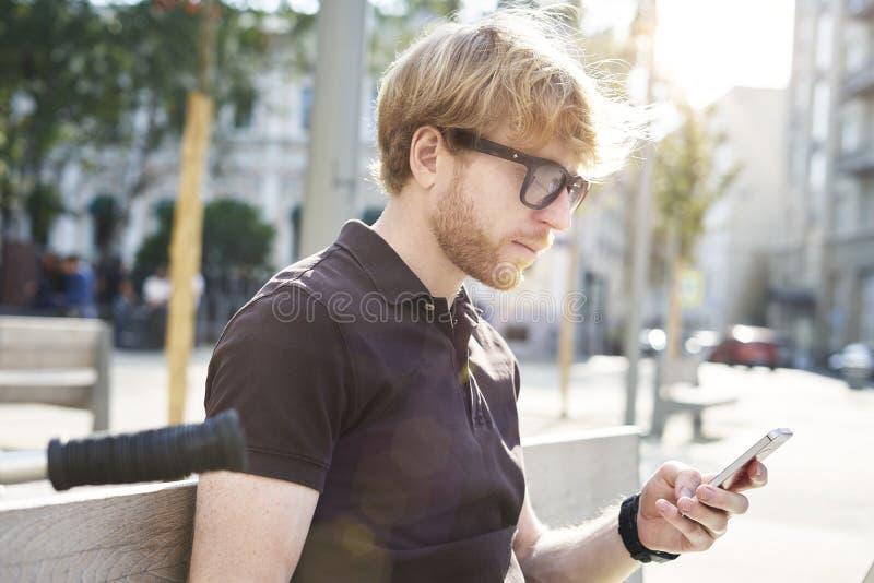 Stilig caucasian hipsterman som använder att sitta för mobiltelefon som är utomhus- i en parkera Sommarsolskendag Begrepp av ungt royaltyfria foton
