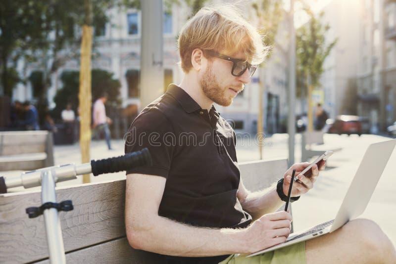 Stilig caucasian hipsterman som använder att sitta för mobiltelefon som är utomhus- i en parkera Sommarsolskendag Begrepp av ungt arkivfoto