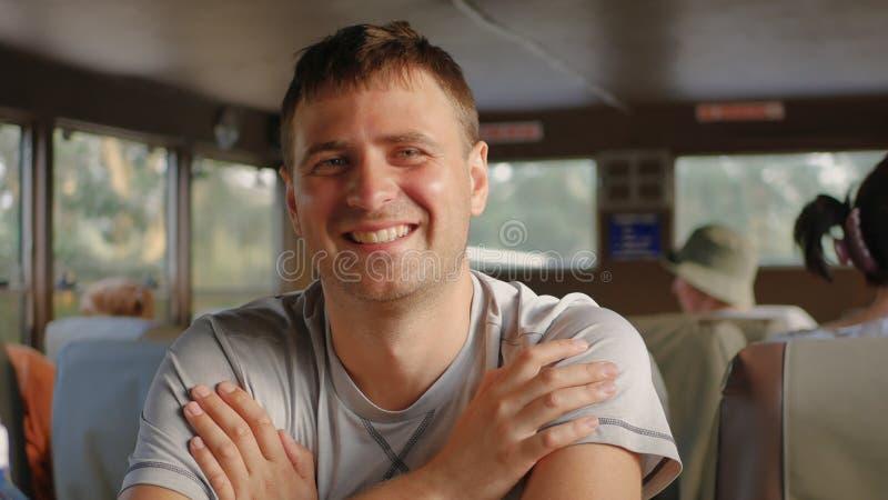 Stilig Caucasian man för stående som ler se kamerasammanträde i transport fotografering för bildbyråer
