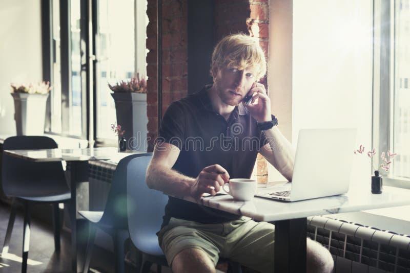 Stilig caucasian man med rött hår genom att använda dator- och smartphonesammanträde i kafét som har kaffe Begrepp av ungt affärs arkivbilder