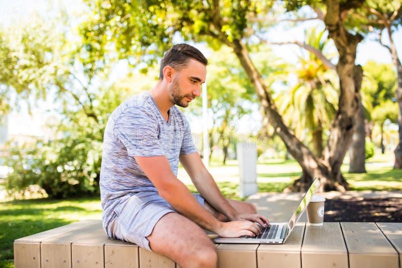 Stilig caucasian man som använder att sitta för bärbar dator som är utomhus- i en parkera Sommarsolskendag Begrepp av ungt affärs royaltyfri foto