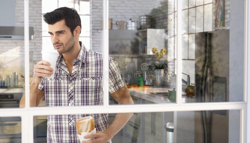 Stilig caucasian man som dricker kaffe på kök fotografering för bildbyråer