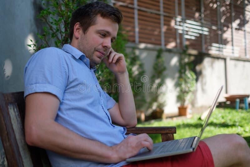 Stilig caucasian ung man som arbetar på bärbara datorn och ler, medan sitta utomhus Begrepp av självarbetsgivaren royaltyfria foton