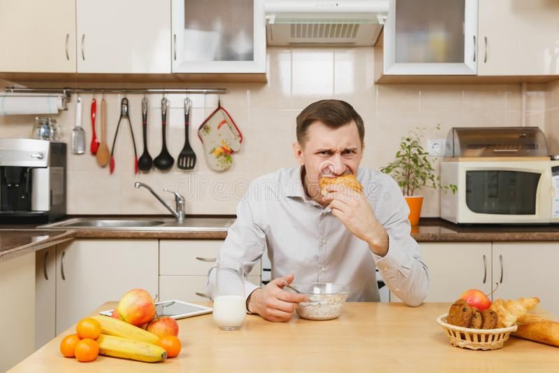 Stilig caucasian ung man som sitter på tabellen Sund livsstil casserole som lagar mat läckert home hemlagat recept mat förbereder fotografering för bildbyråer