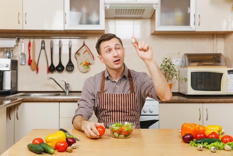 Stilig caucasian ung man som sitter på tabellen Sund livsstil casserole som lagar mat läckert home hemlagat recept mat förbereder arkivbilder
