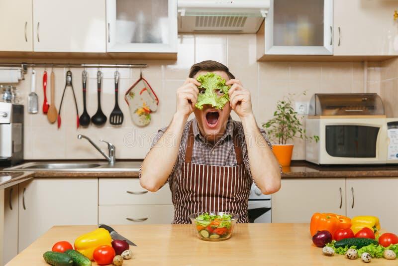 Stilig caucasian ung man som sitter på tabellen Sund livsstil casserole som lagar mat läckert home hemlagat recept mat förbereder royaltyfri fotografi